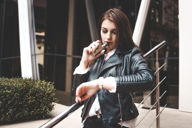 Портрет серьезной девушки, которая использует электронную сигарету и смотрит на часы