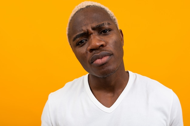 オレンジの深刻なハンサムな黒金髪アフリカ人クローズアップの肖像画