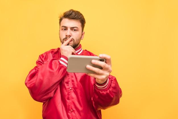 Портрет серьезного человека с бородой, в красной куртке, стоит со смартфоном в руке на желтом
