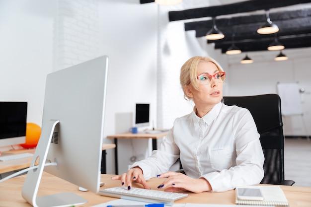 コンピューターとオフィスで働く深刻な成熟した実業家の肖像画