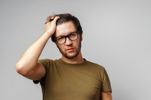 Портрет серьезного задумчивого молодого человека на сером