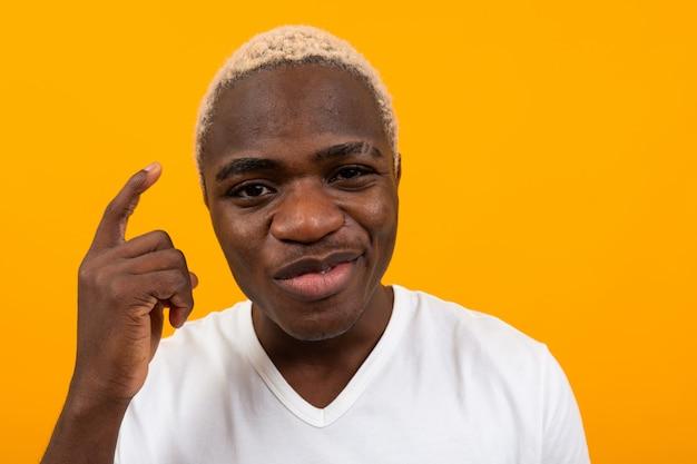 オレンジの深刻な思考のハンサムな黒金髪アフリカ人クローズアップの肖像画