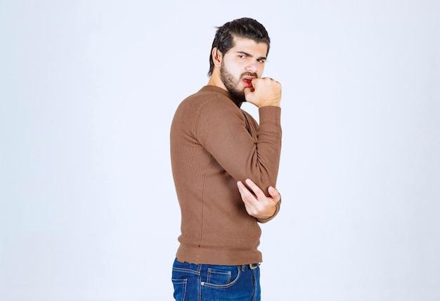 Портрет модели серьезного молодого человека стоя и глядя.