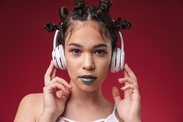 ブルゴーニュの赤い壁に隔離されたヘッドフォンで音楽を聴いている深刻な若いパンク10代の少女の肖像画。