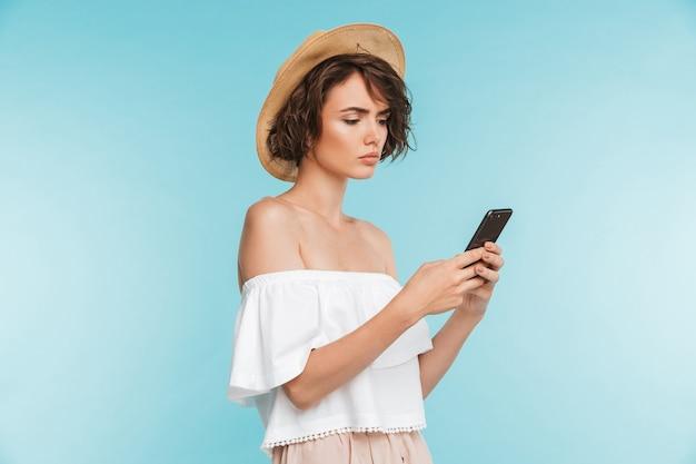 Портрет серьезной молодой женщины с помощью мобильного телефона