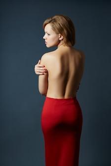 어두운 배경에 섹시 성인 금발 여자의 초상화. 짧은 머리를 가진 자신감 비즈니스 레이디