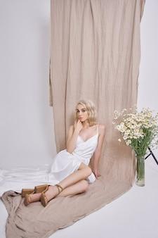 野生の花の花瓶の近くの美しい白いドレスを着たセクシーなブロンドの肖像画。美しい自然なメイクでロマンチックな女の子