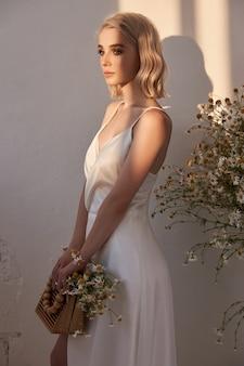 夕方の太陽の下で美しい白いドレスを着たセクシーなブロンドの女性の肖像画。美しい自然なメイクでロマンチックな女の子
