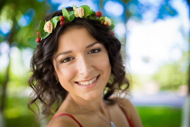 緑の公園で彼女の髪に花を持つセクシーなブルネットの肖像画。女の子の春。