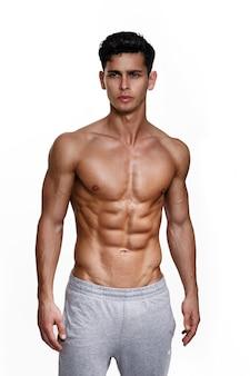 근육질의 몸이 포즈와 섹시 잘 생긴 갈색 머리 젊은 남자의 초상화
