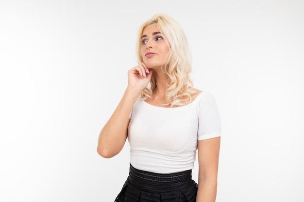 Портрет сексуальной леди в белом топе и черной юбке, позирующей держаться за подбородок на белой студии с копией пространства