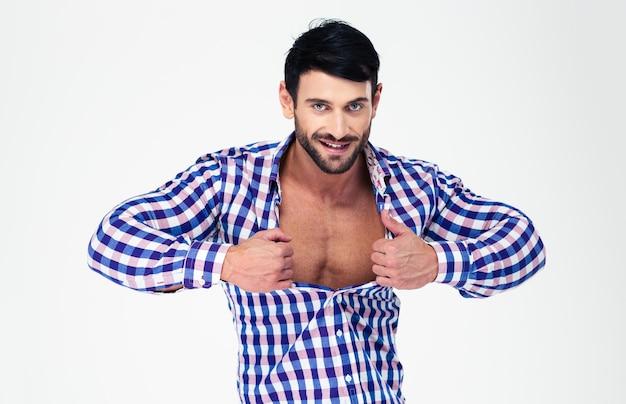 Портрет сексуального мачо, расстегивающего рубашку, изолированного на белой стене