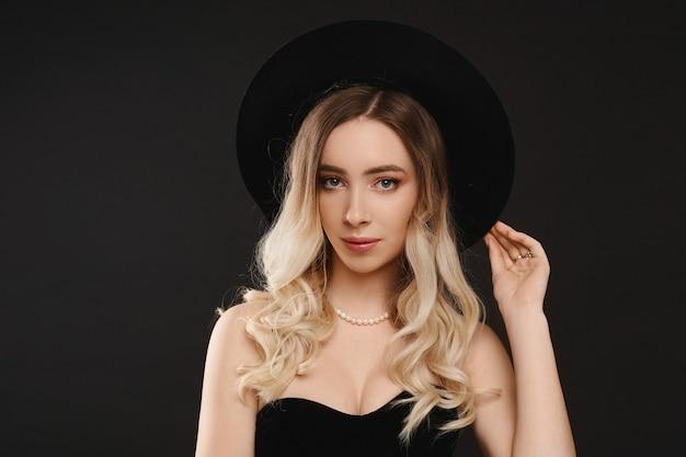 黒のボディスーツと黒の背景に黒のスタイリッシュな帽子で完璧なスリムなボディを持つセクシーなモデルの女性の肖像画