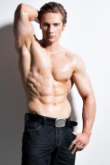 Портрет сексуального мускулистого красавца с руками за головой, позирует на белой стене.