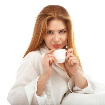 白で隔離のベッドでコーヒーを飲むセクシーな赤い髪の少女の肖像画