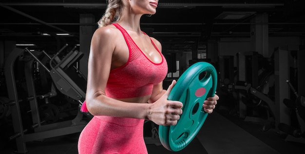 Портрет сексуальной спортсменки, позирующей в тренажерном зале с диском со штангой. концепция фитнеса.