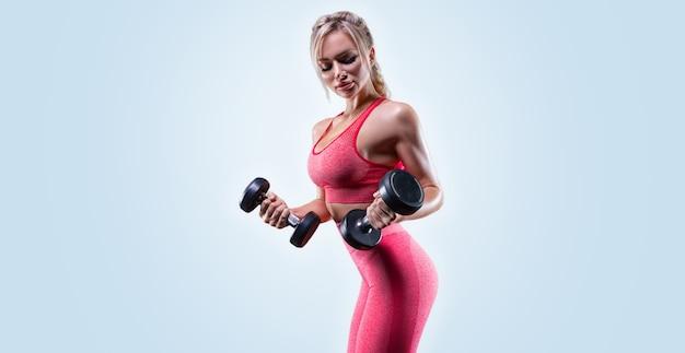 Портрет сексуальной спортсменки, позирующей с гантелями. концепция фитнеса.