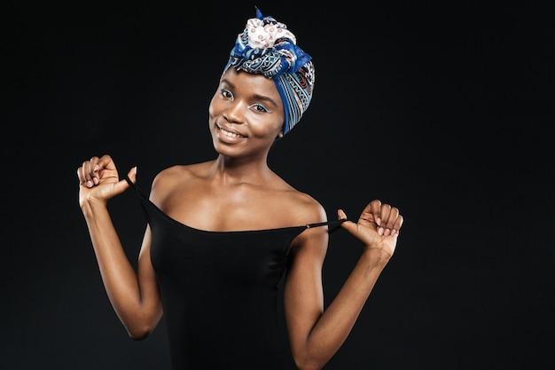 Портрет сексуальной женщины в черном боди позирует изолированной на черной стене