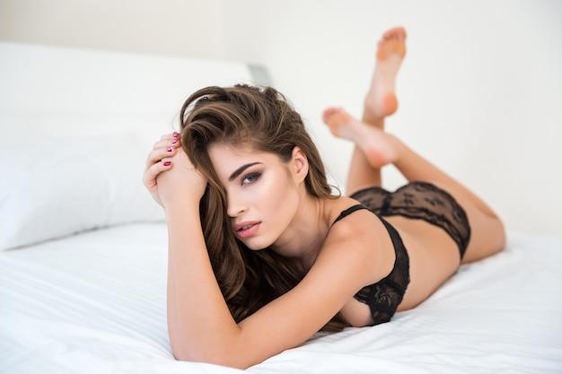Портрет сексуальной женщины в нижнем белье и с длинными волосами, лежащей на кровати и смотрящей на cmaera