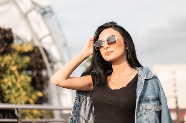 야외에서 세련 된 옷을 입고 유행 선글라스에 섹시 한 젊은 갈색 머리 여자의 초상화. 아름 다운 hipster 소녀는 화창한 날을 즐깁니다.