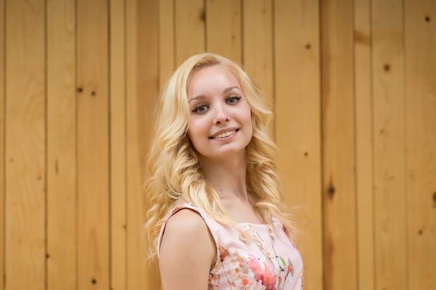 木の板の背景にセクシーな若い女性金髪の肖像画