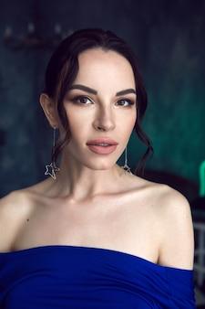 着用した壁に青いドレスを着た星の形のイヤリングを持つセクシーな少女の肖像画