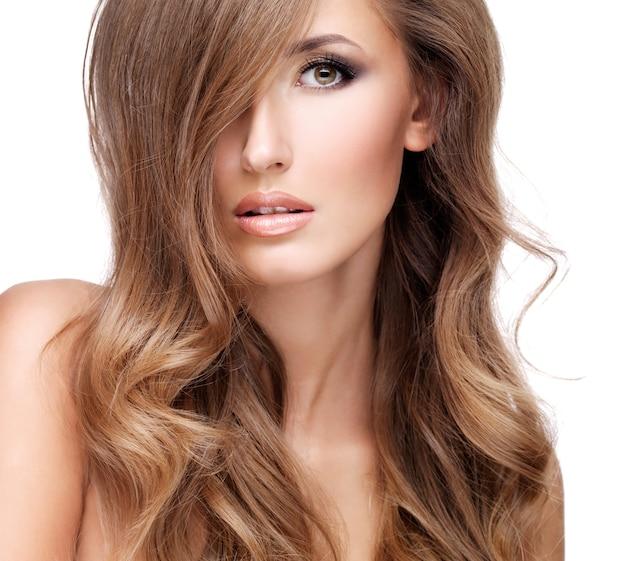 美しい長い茶色の髪を持つセクシーな若い女性の肖像画。クローズアップ、白で隔離