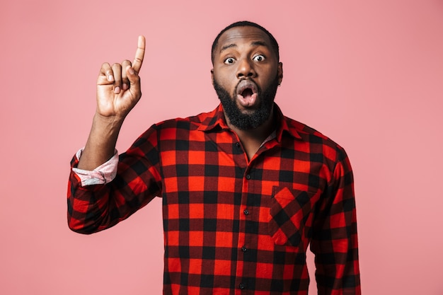 ピンクの壁の上に孤立して立っている格子縞のシャツを着て、身振りで示す、指を指すショックを受けたアフリカ人の肖像画