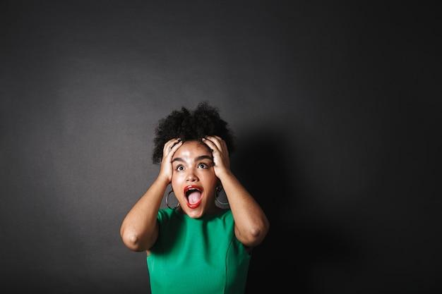 Портрет шокированной афро-американской женщины в платье, стоящей над черной стеной