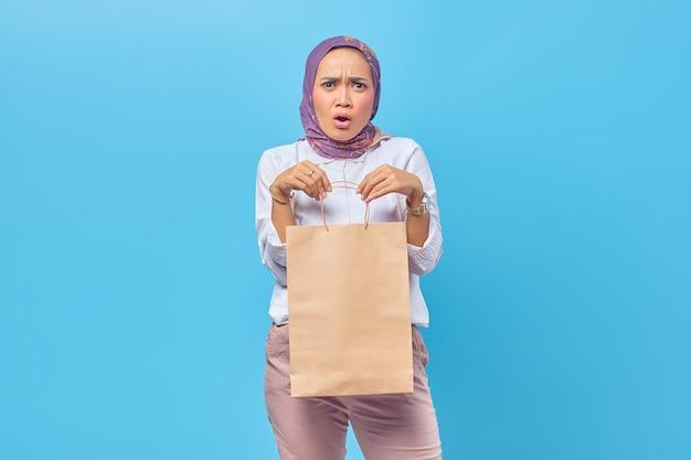 先を見据えて買い物袋を運ぶショックを受けて驚いた若いアラビアの学生の肖像画