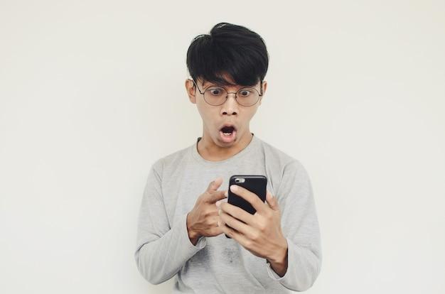 스마트폰을 보고 충격을 받은 아시아 남자의 초상화