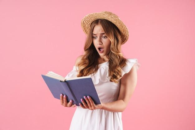 Портрет потрясенной запутанной милой молодой красивой женщины, позирующей изолированной над розовой настенной книгой для чтения.