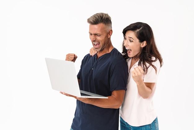 Портрет потрясенной эмоциональной веселой взрослой влюбленной пары, изолированной над белой стеной с помощью портативного компьютера, делает жест победителя.