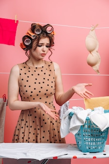 服を着てバスケットを指しているショックを受けた少女の肖像画。ピンクの背景に彼女の髪にカーラーを持つ主婦。