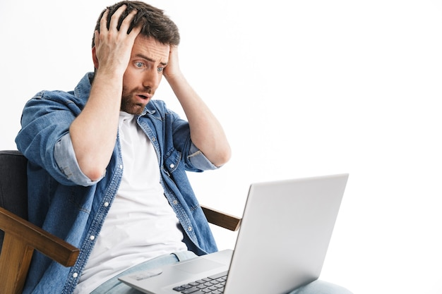 白い壁に隔離された椅子に座って、ラップトップコンピューターで作業してカジュアルな服を着てショックを受けたハンサムなひげを生やした男の肖像画