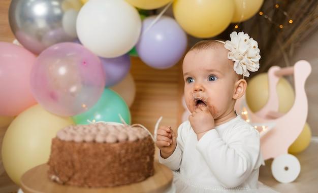 Портрет потрясенной маленькой девочки с грязным лицом, едящей торт руками