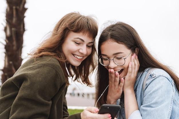 Портрет потрясенных удивленных эмоциональных молодых симпатичных друзей женщин-студентов, идущих на открытом воздухе, слушая музыку в наушниках с помощью мобильного телефона.