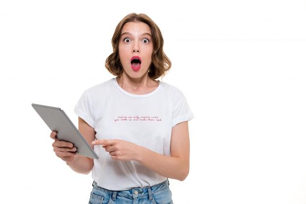 Портрет потрясенной молодой девушки, держащей планшетный компьютер