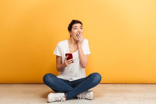 携帯電話を保持しているショックを受けた若い女性の肖像画
