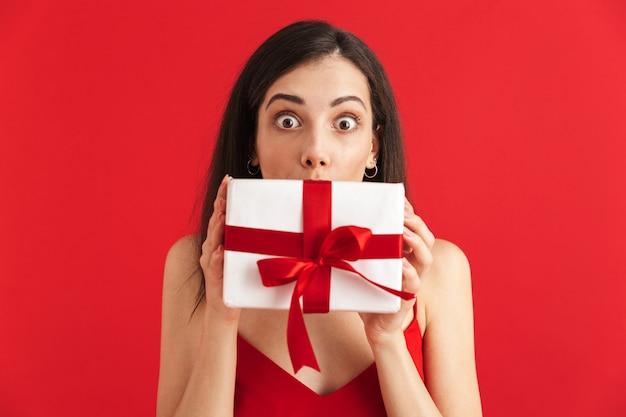 고립 된 선물 상자를 들고 드레스에 충격 된 젊은 여자의 초상화