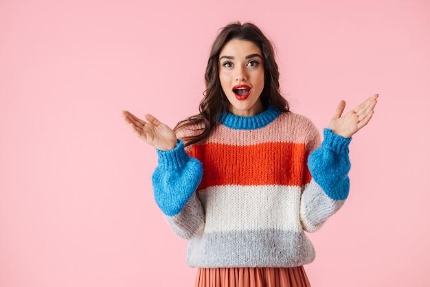 Портрет потрясенной молодой женщины в свитере, стоящей изолированно над розовым