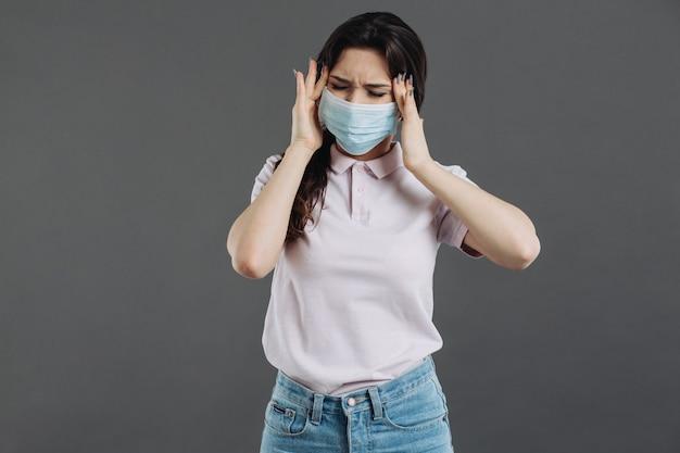 Портрет молодой женщины больной головной боли нося медицинскую маску. пандемия 2019 коронавирус 2019-нков концепции.