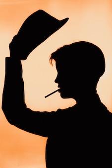 Портрет силуэта девушки в шляпе с сигаретой.