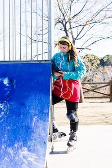 도시 스케이트장에서 헤드폰으로 음악을 듣고 스케이트 소녀의 초상화. 파란색 재킷과 파란색 양모 모자를 착용했습니다. 도시 스케이트 개념.