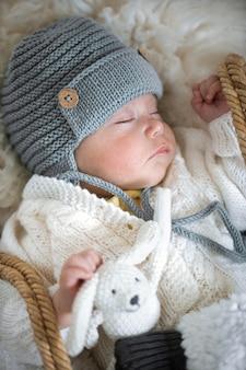 ハンドルにニットのおもちゃを持った暖かいニット帽で眠っている赤ちゃんの肖像画をクローズアップ。