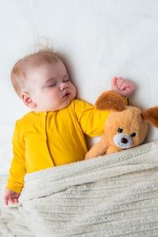 Портрет спящего младенца в объятиях с игрушкой