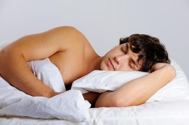 彼の寝室で眠っているハンサムな男の肖像画