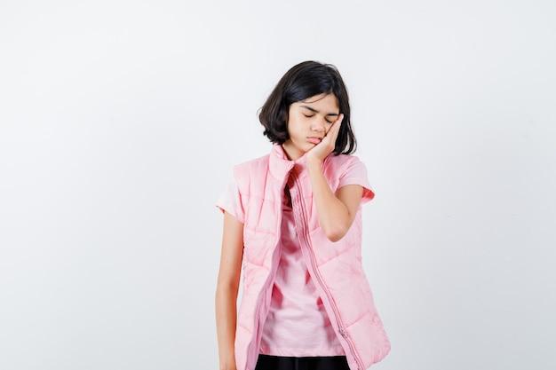 흰색 티셔츠와 호흡기 조끼에 졸린 어린 소녀의 초상화