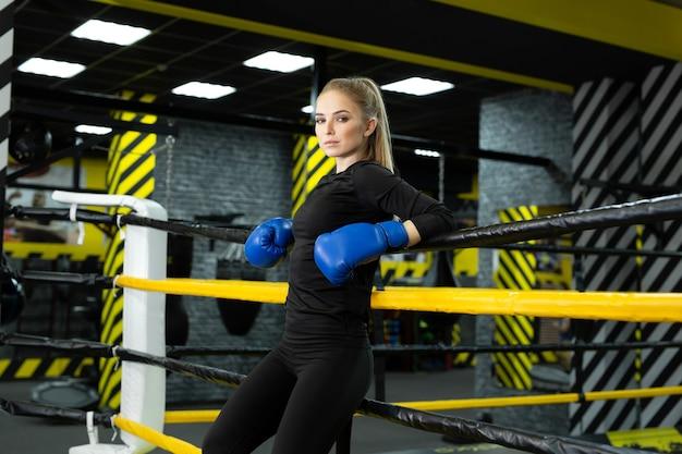 ロープに寄りかかって青いボクシンググローブの細い運動選手の肖像画