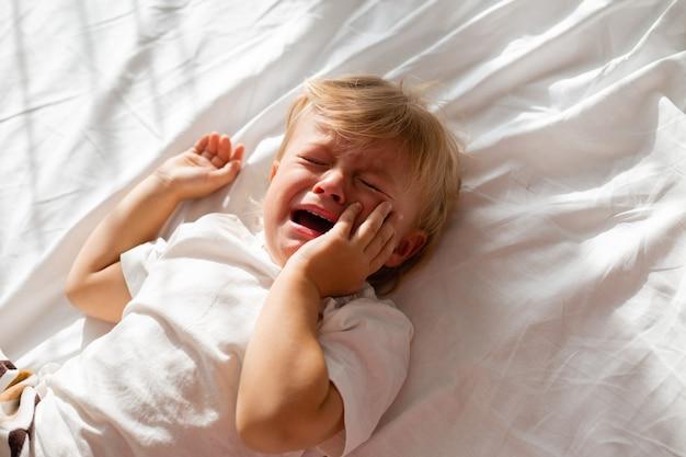 ベッドの白いシートに仰向けに横たわっている白いtシャツを着た金髪の小さな泣いている男の子の肖像画